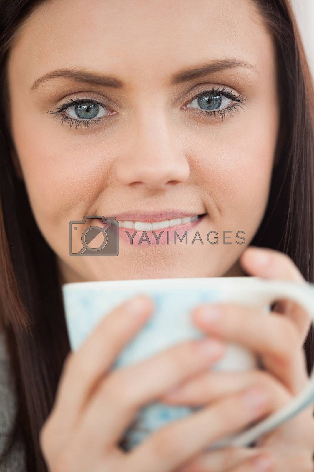 Smiling girl holding a cup of coffee  by Wavebreakmedia
