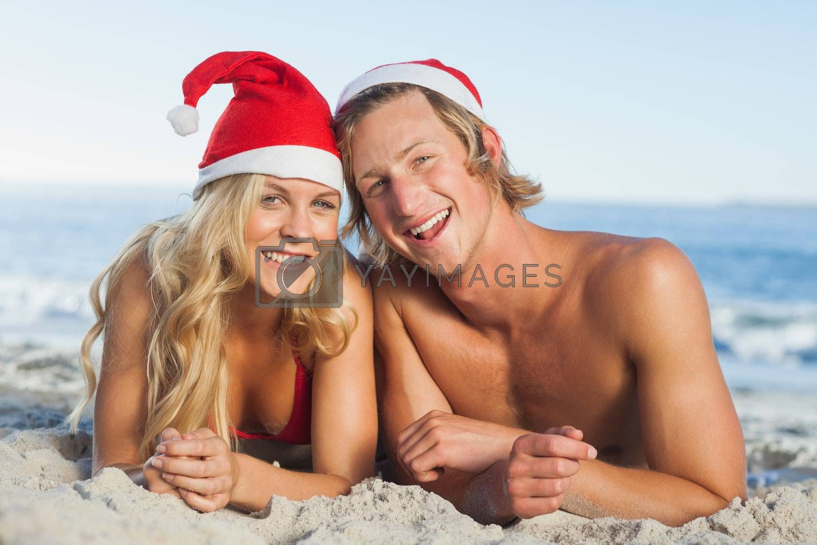 Couple lying on beach wearing christmas hats by Wavebreakmedia