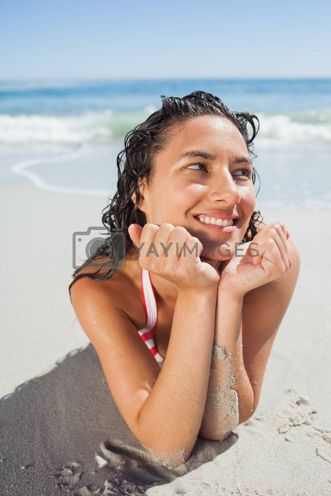 Close up view of smiling woman lying down on beach by Wavebreakmedia