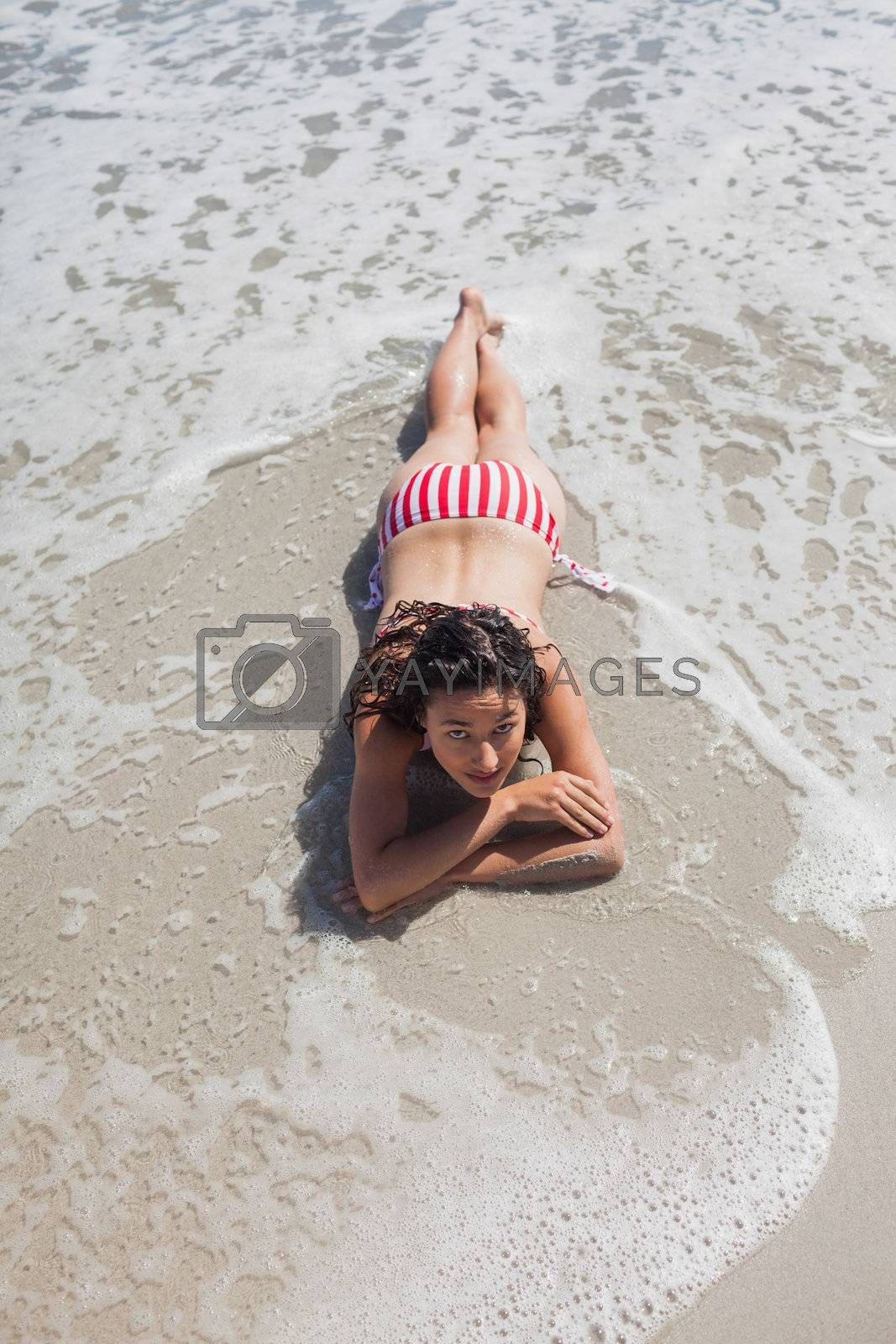 High angle view of woman lying down on beach by Wavebreakmedia