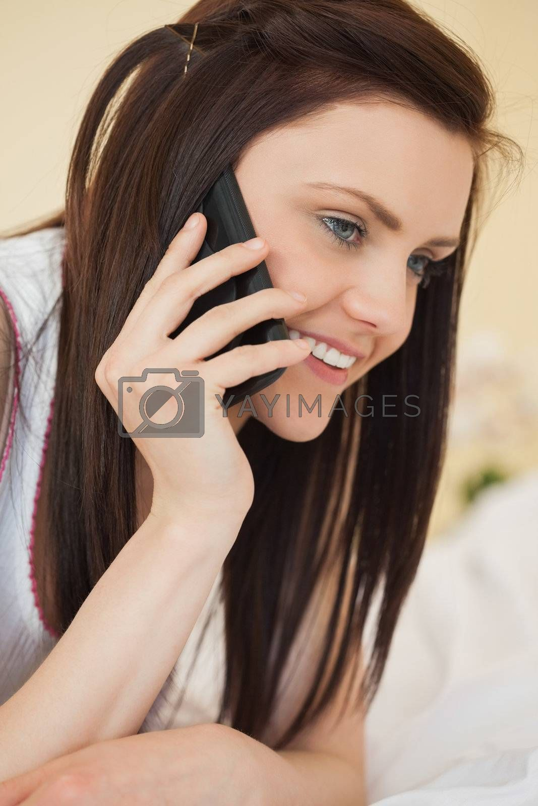 Smiling girl calling someone with a mobile phone lying on a bed by Wavebreakmedia