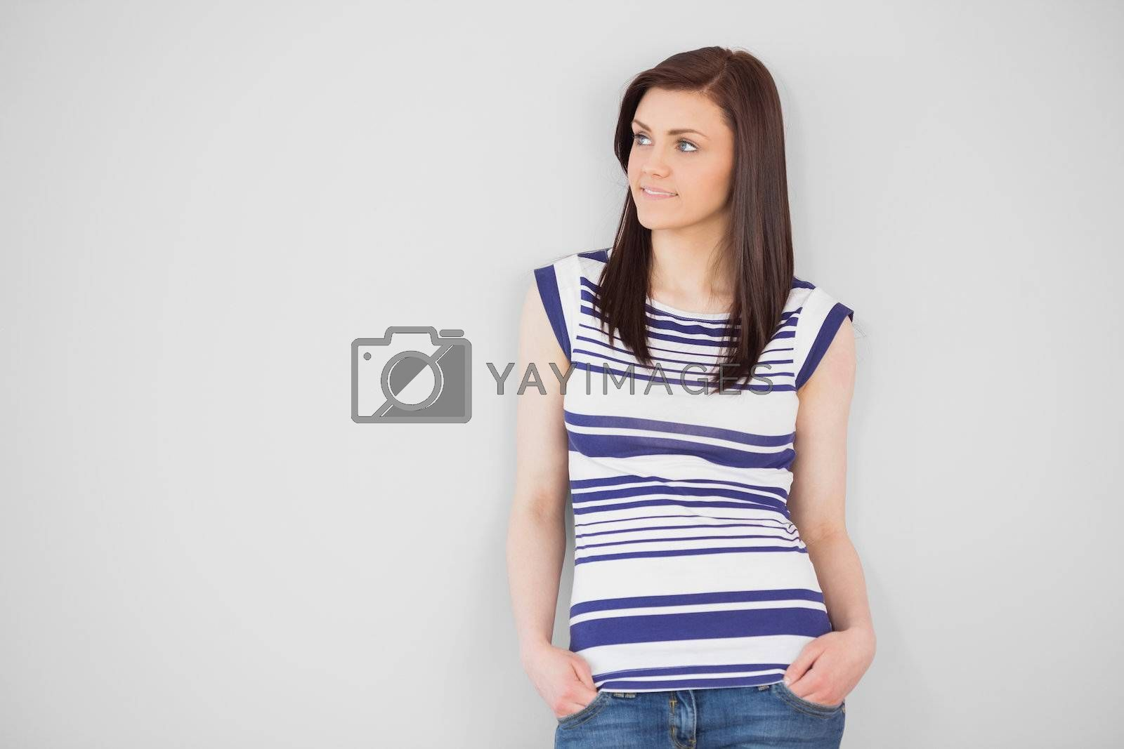 Thoughtful stylish girl standing and looking away by Wavebreakmedia