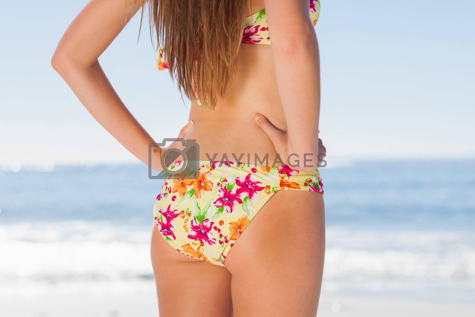 Beautiful woman on the beach in floral bikini by Wavebreakmedia