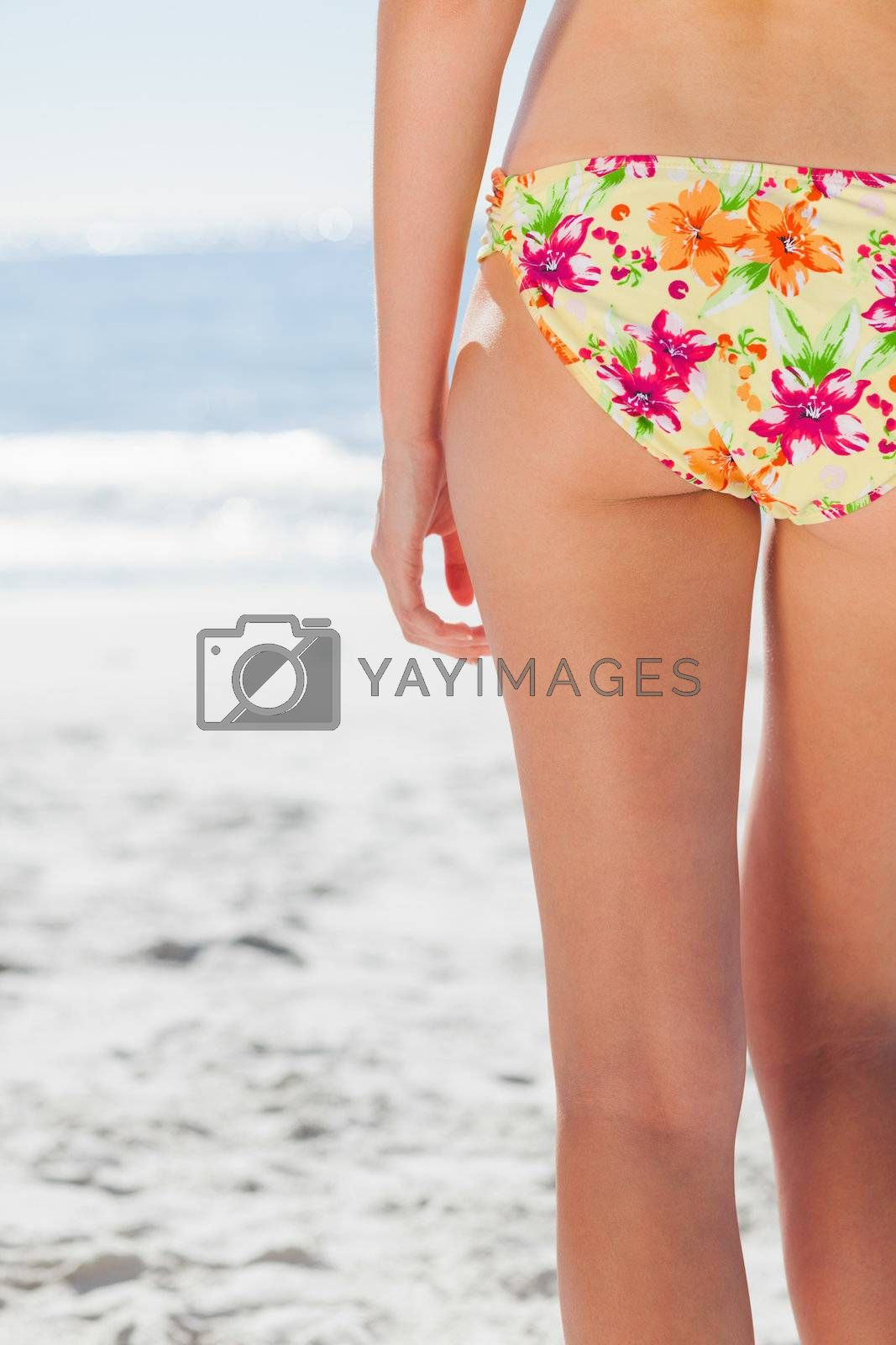 Woman in floral bikini standing back to camera by Wavebreakmedia