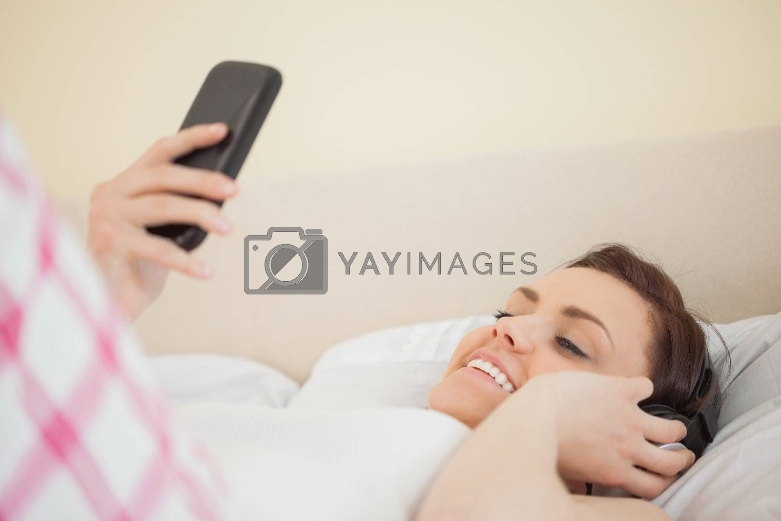Happy girl listening to music and using a mobile phone lying on a bed by Wavebreakmedia