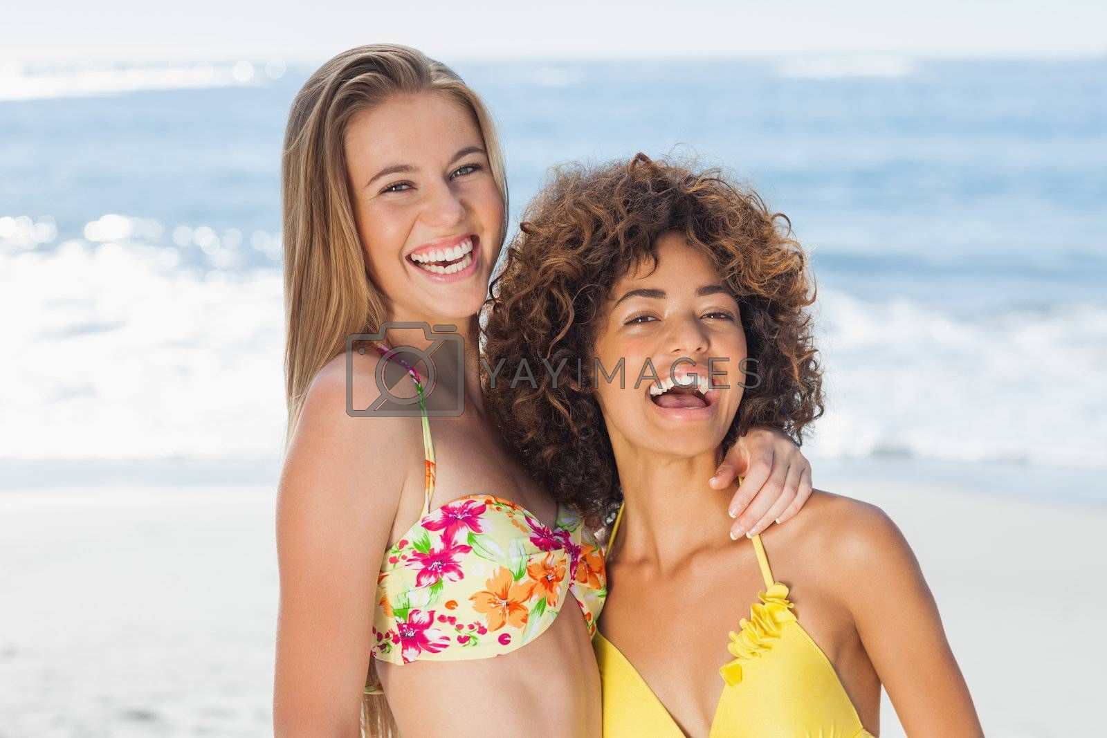 Two smiling friends posing together by Wavebreakmedia