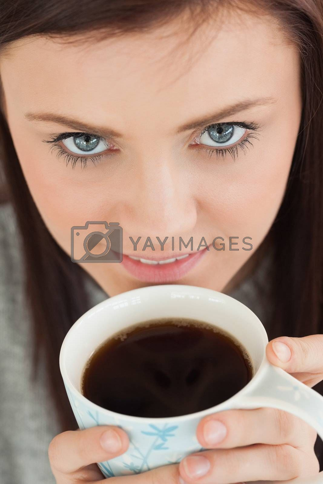 Smiling girl drinking a cup of coffee by Wavebreakmedia