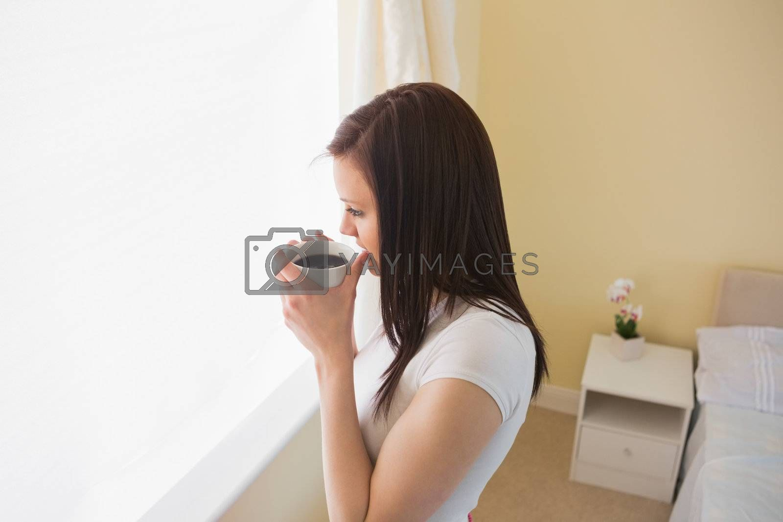 Girl drinking a cup of coffee in a bedroom by Wavebreakmedia