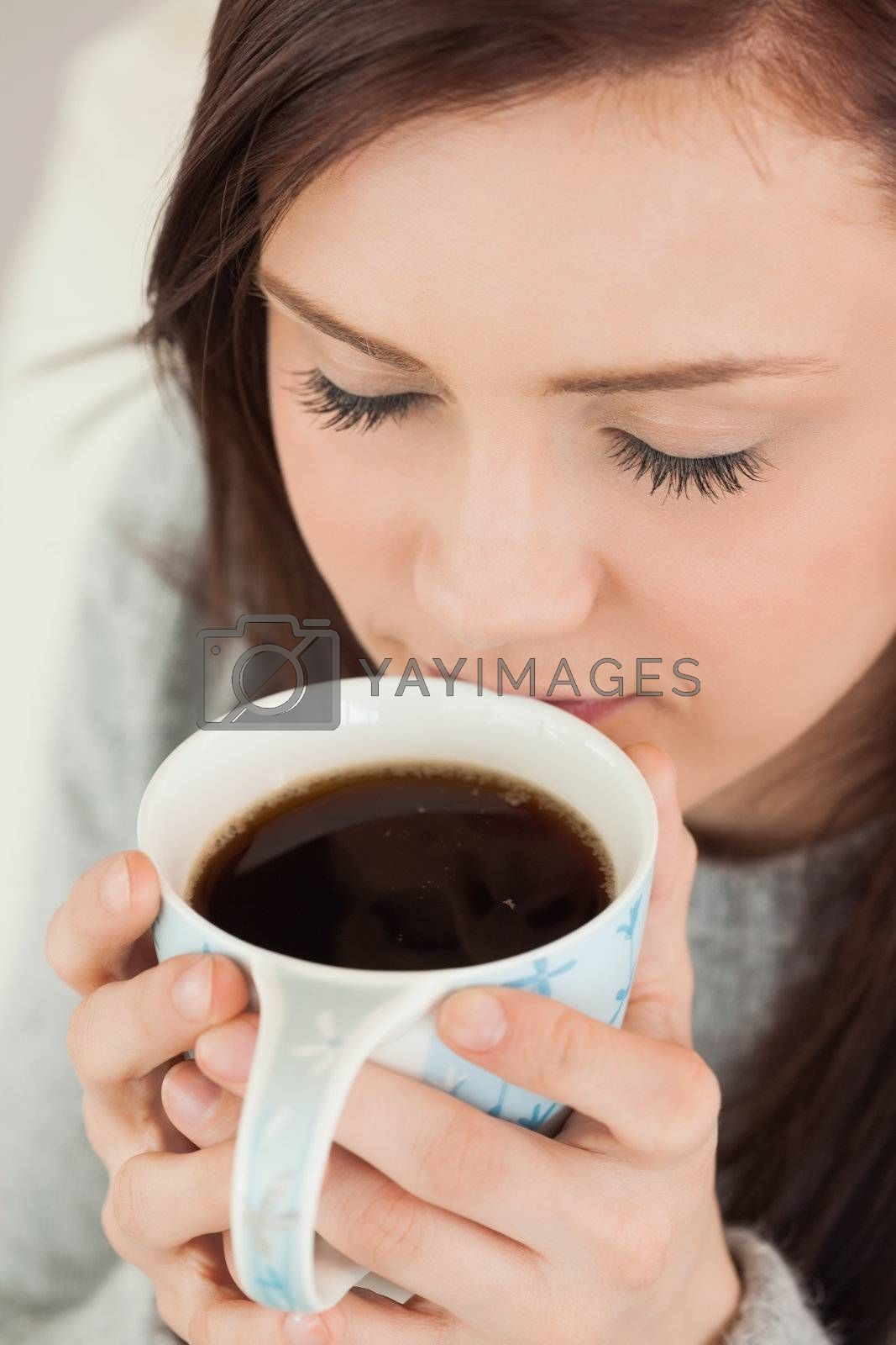 Relaxed girl drinking a cup of coffee by Wavebreakmedia