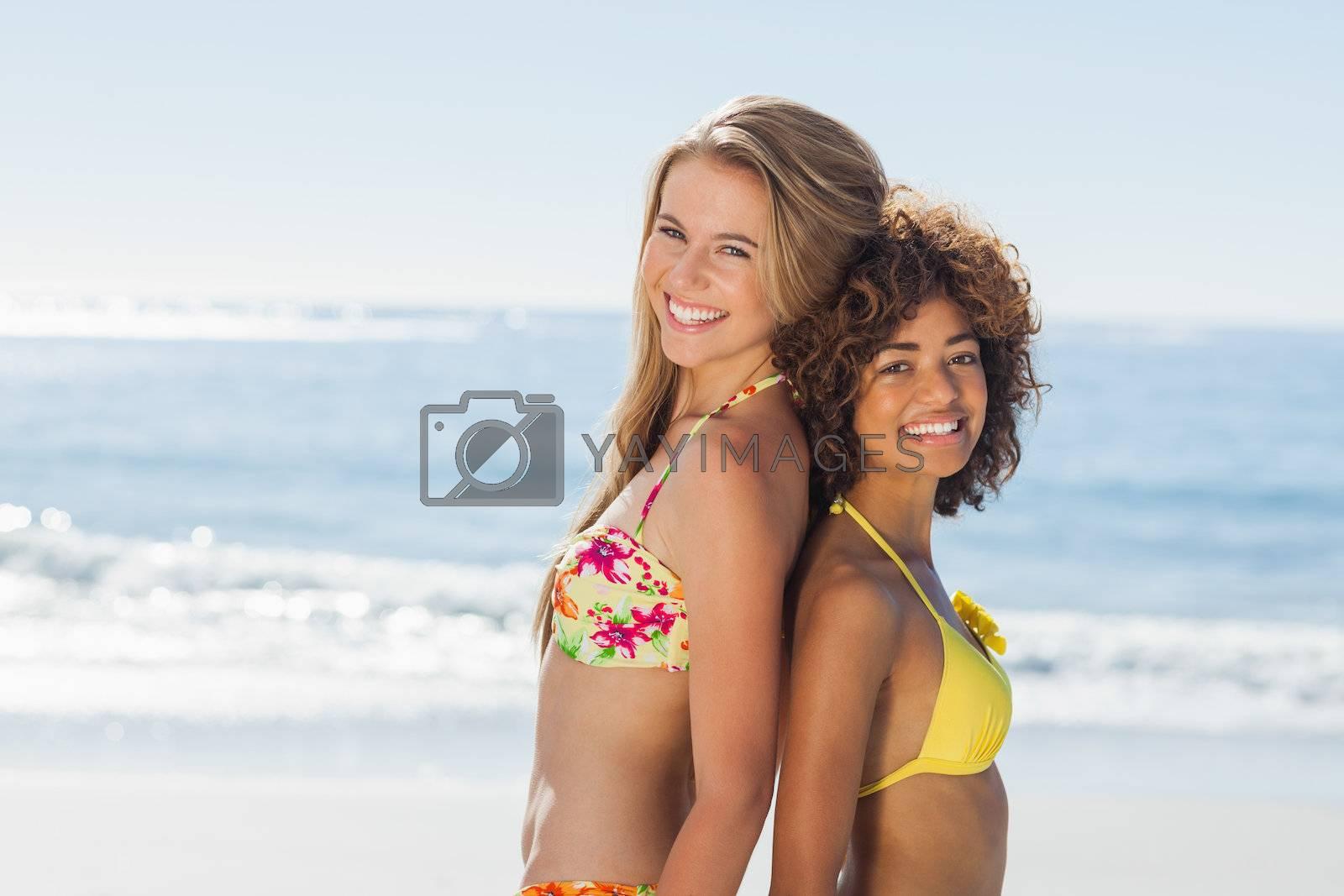 Smiling friends in bikinis standing back-to-back by Wavebreakmedia