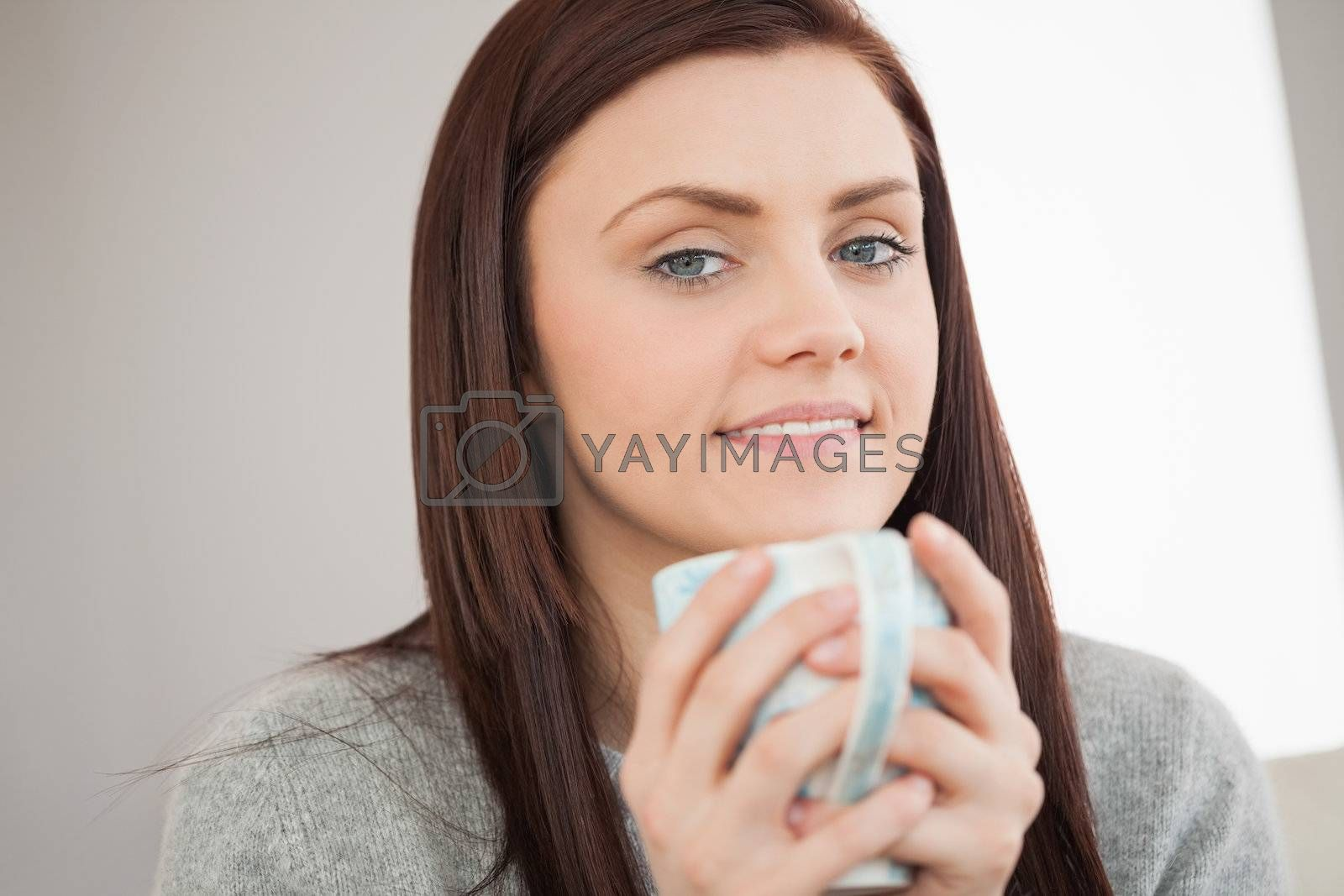 Thoughtful girl holding a cup of coffee and looking at camera by Wavebreakmedia