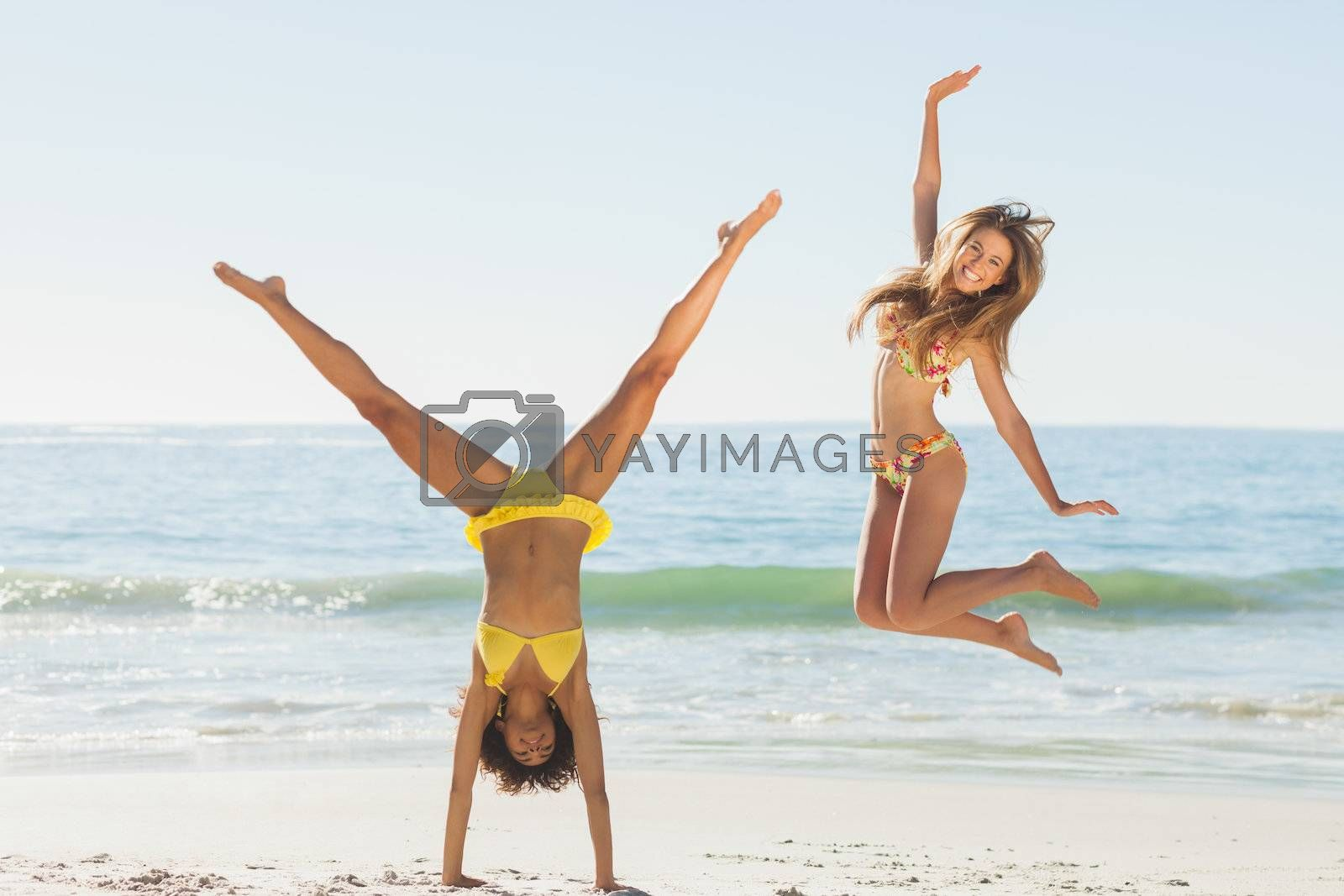 Friends in bikinis jumping and doing handstand by Wavebreakmedia