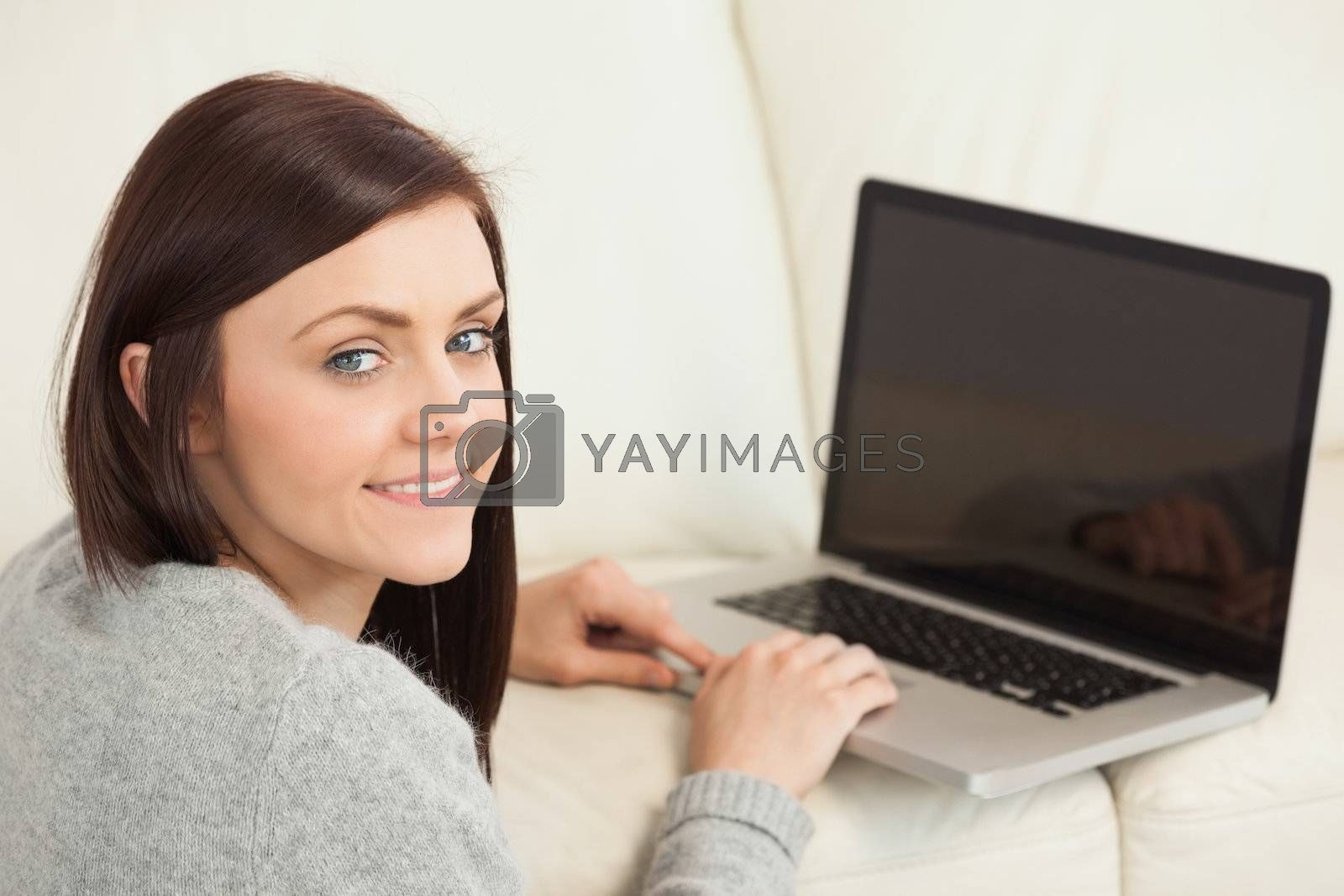 Smiling girl using a laptop on a sofa looking at camera by Wavebreakmedia