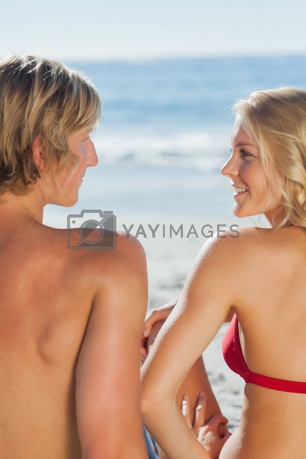Attractive couple relaxing on the beach together by Wavebreakmedia
