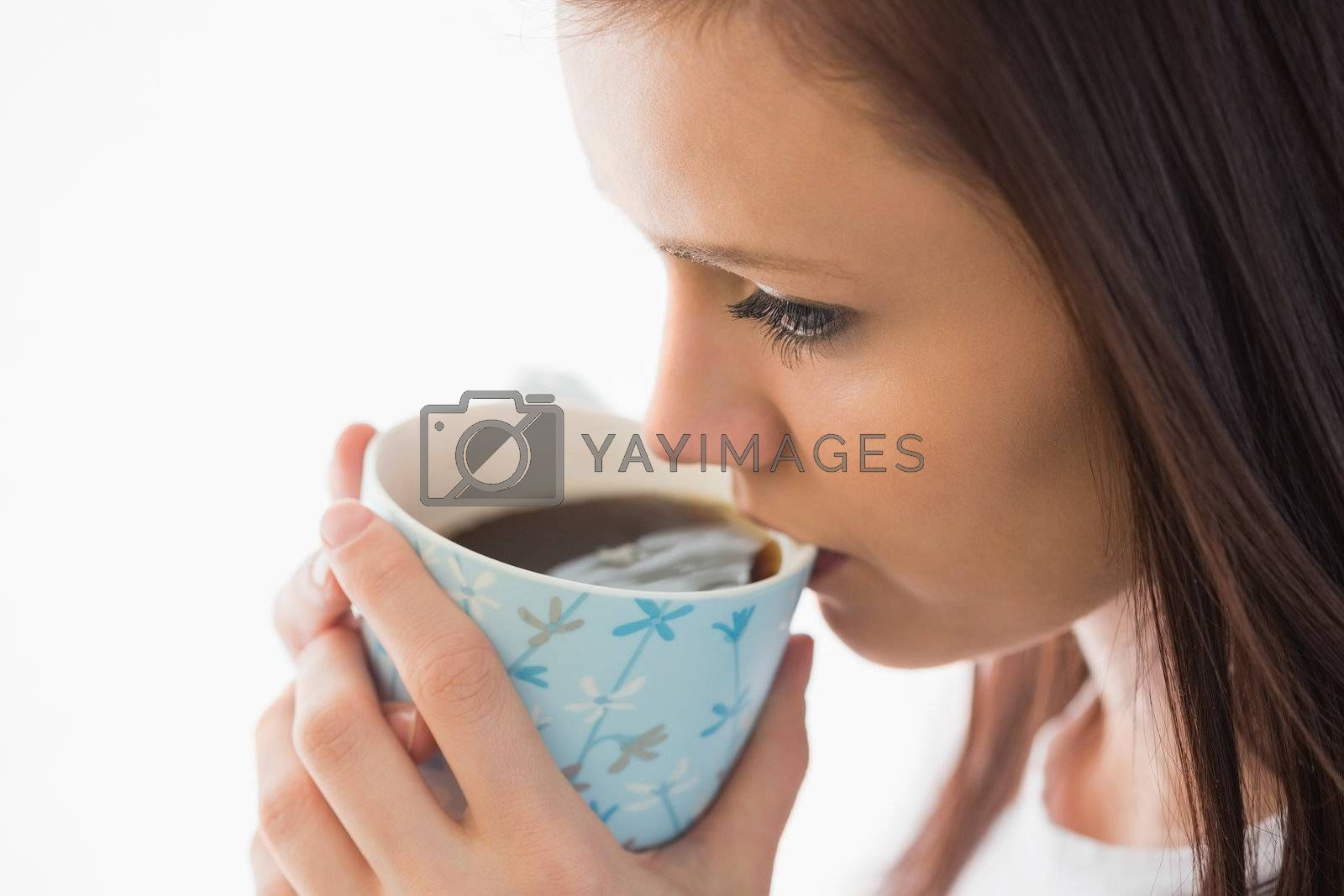 Calm girl drinking a cup of coffee by Wavebreakmedia