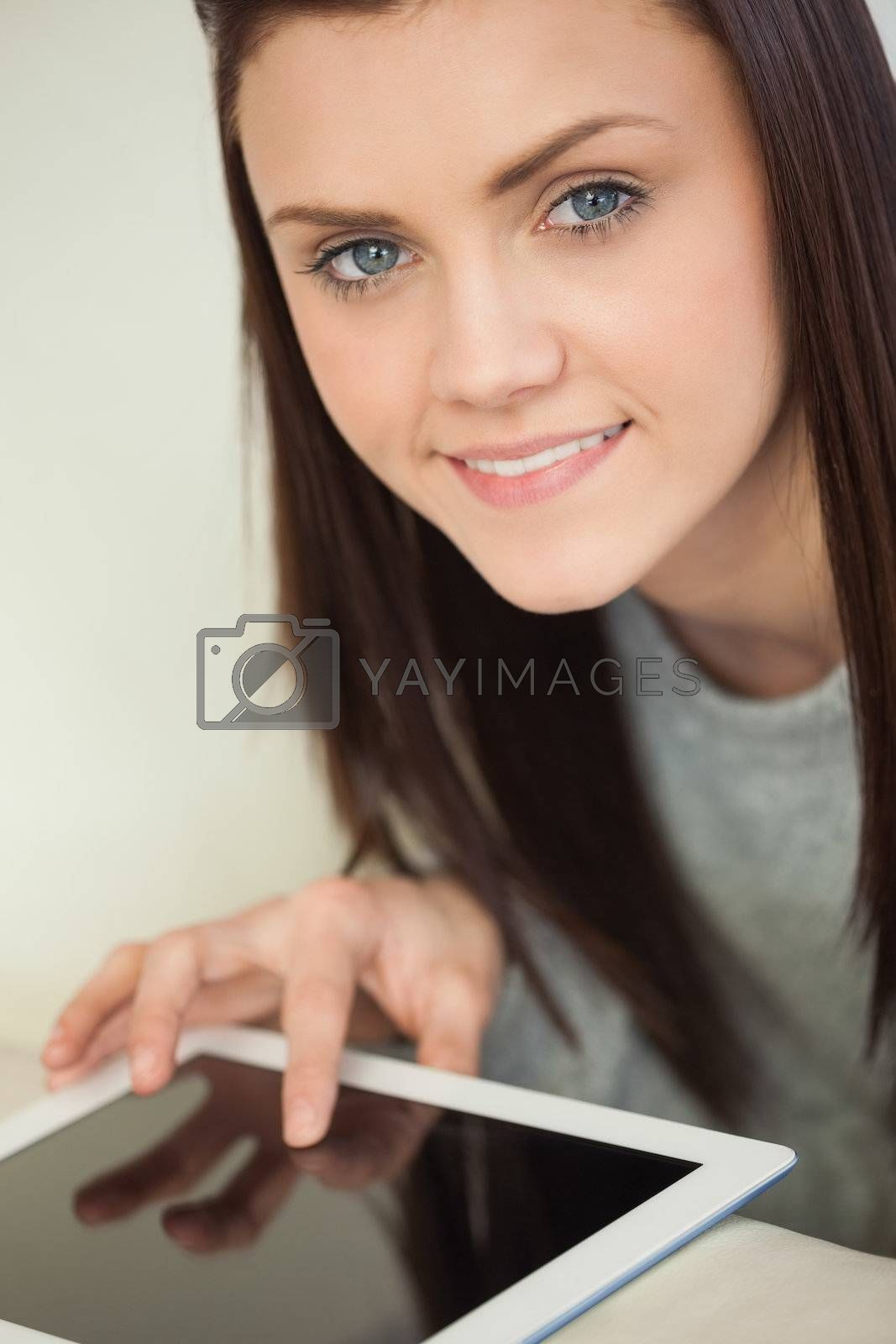 Smiling pretty girl using a tablet pc on a sofa looking at camera by Wavebreakmedia