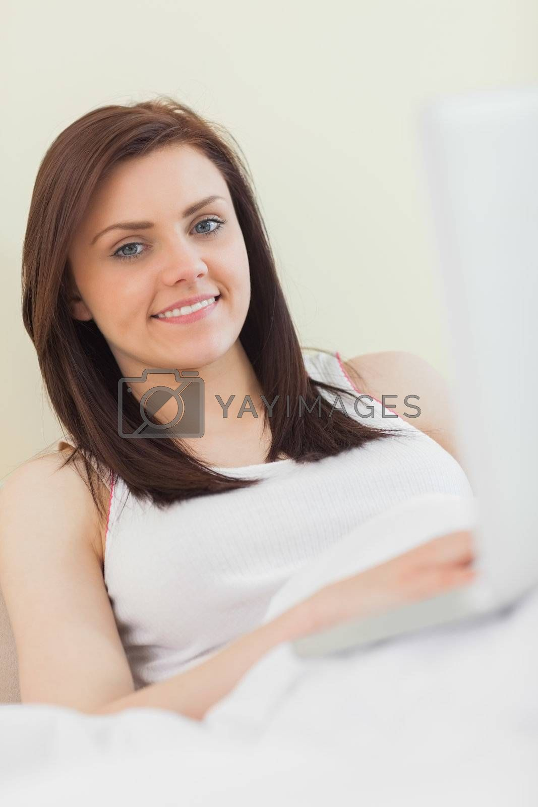 Content girl looking at camera and using a laptop lying on a bed by Wavebreakmedia