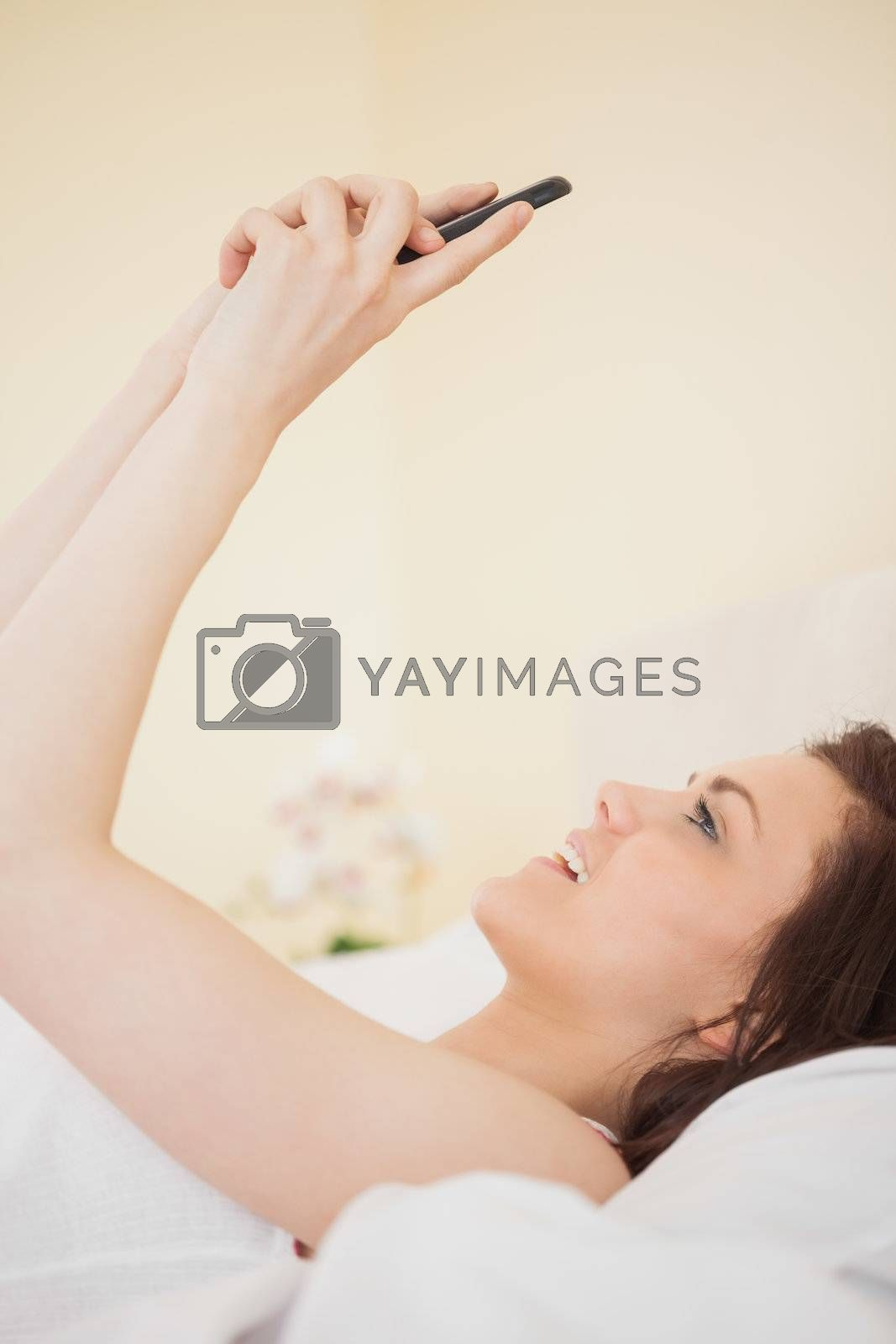 Happy girl using a mobile phone lying on a bed by Wavebreakmedia