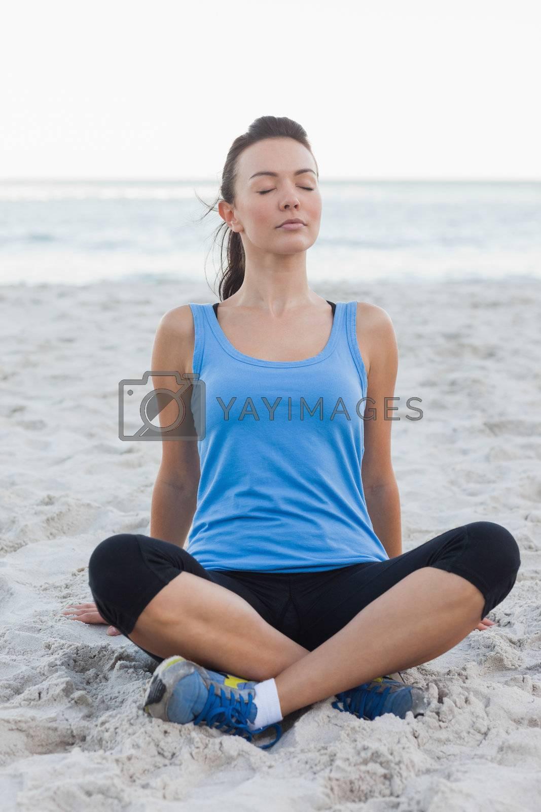 Sporty woman sitting in sand  by Wavebreakmedia