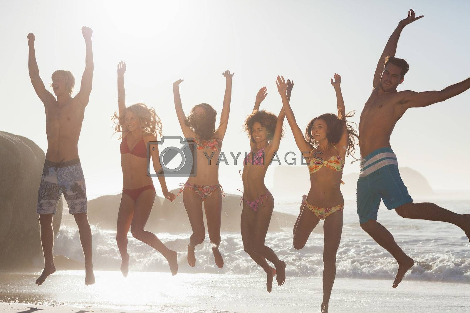 Laughing friends jumping by Wavebreakmedia