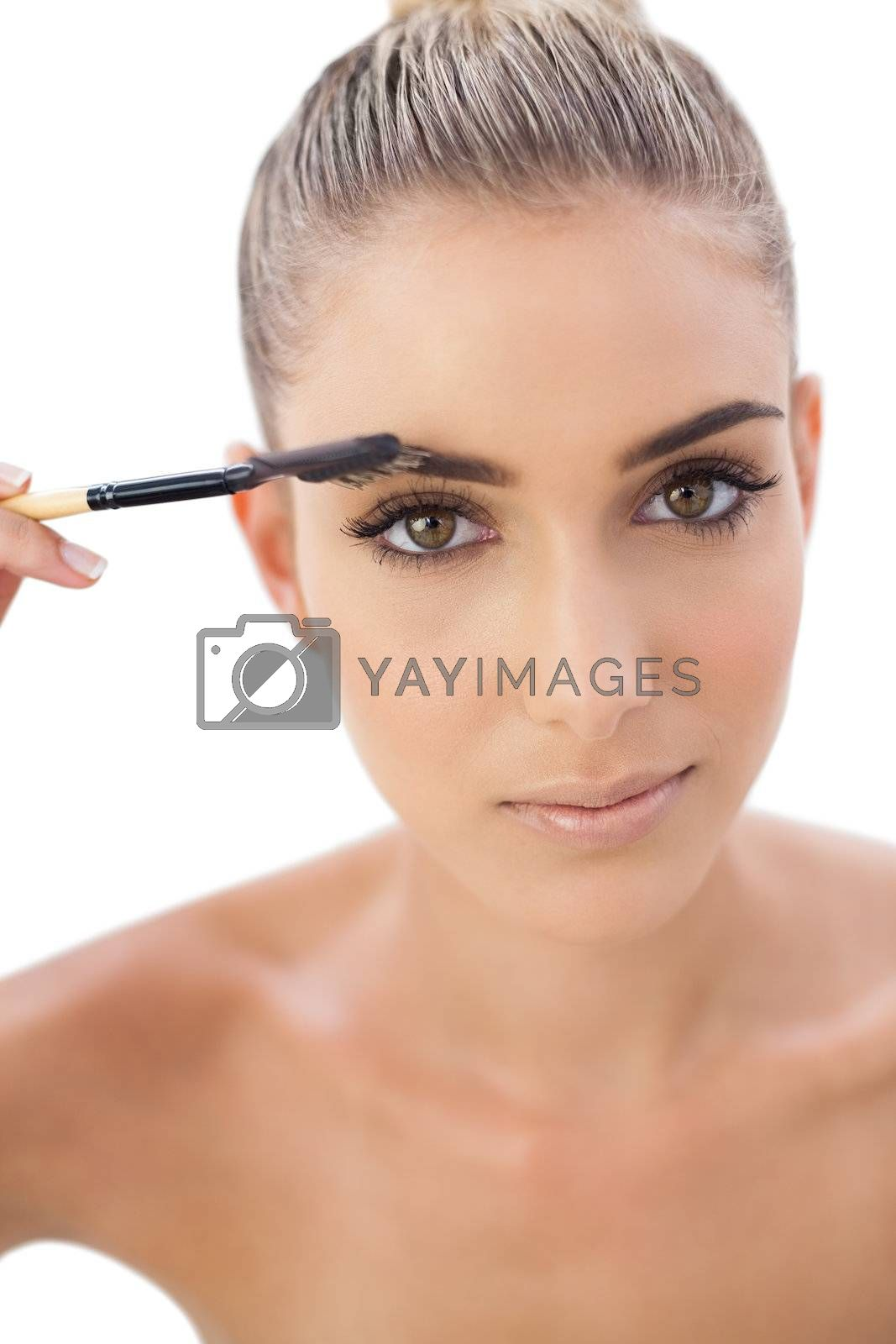 Serious woman applying make up on her eyebrows by Wavebreakmedia