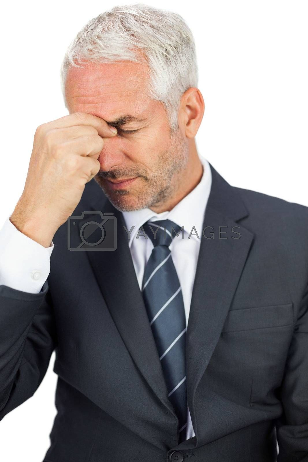 Upset businessman closing his eyes and holding his head by Wavebreakmedia