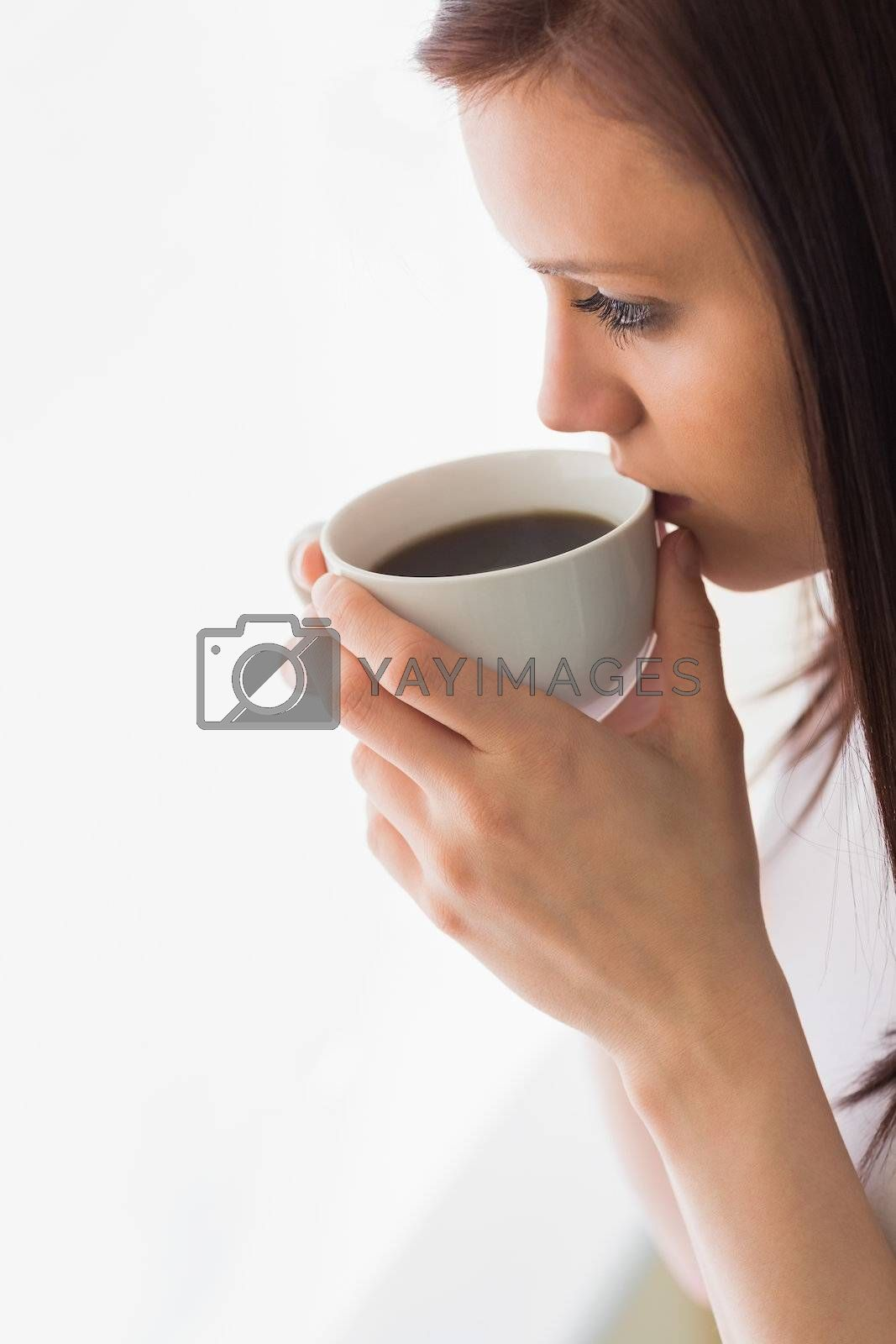 Thoughtful teen holding a cup of coffee looking away by Wavebreakmedia