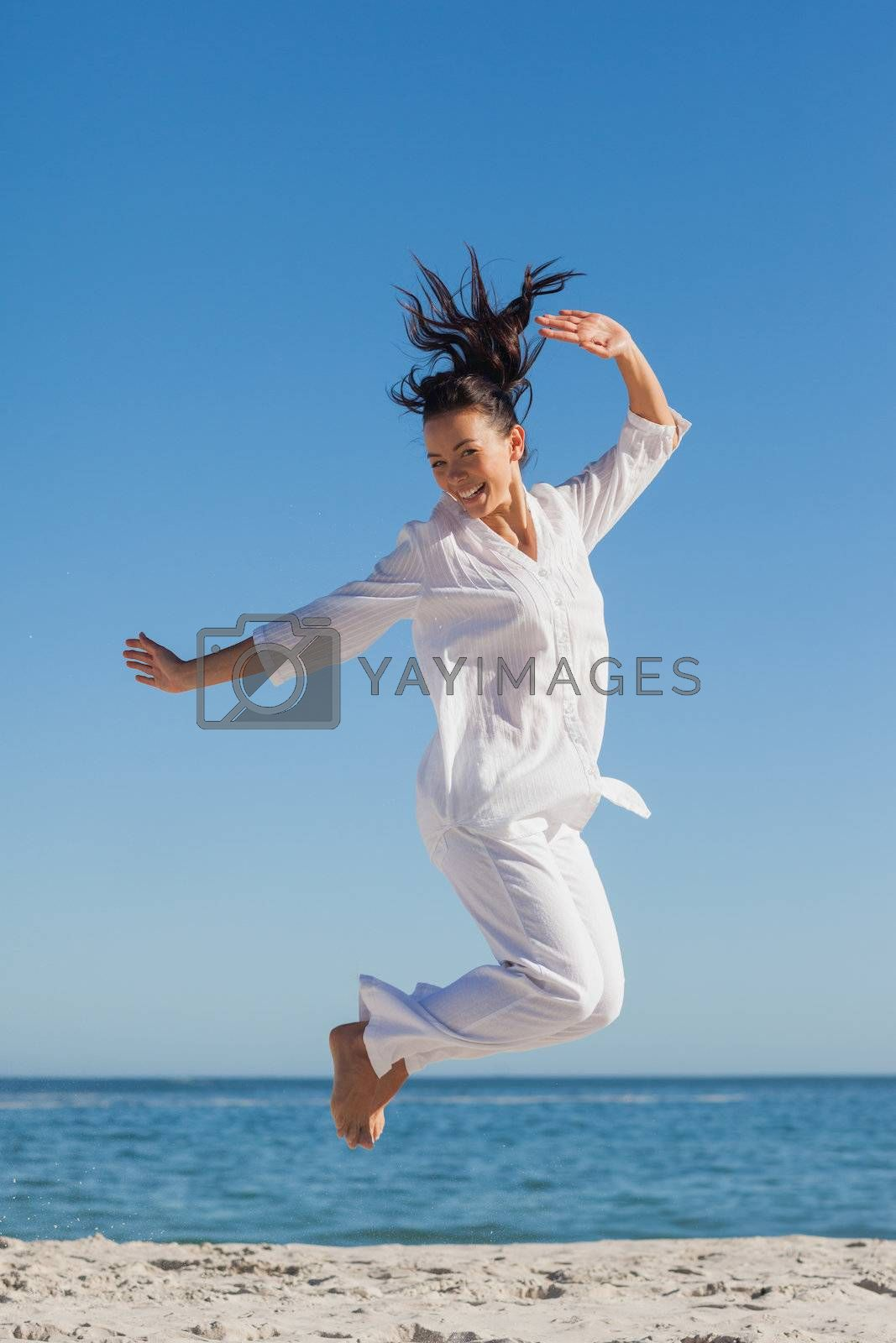 Woman jumping on the beach  by Wavebreakmedia