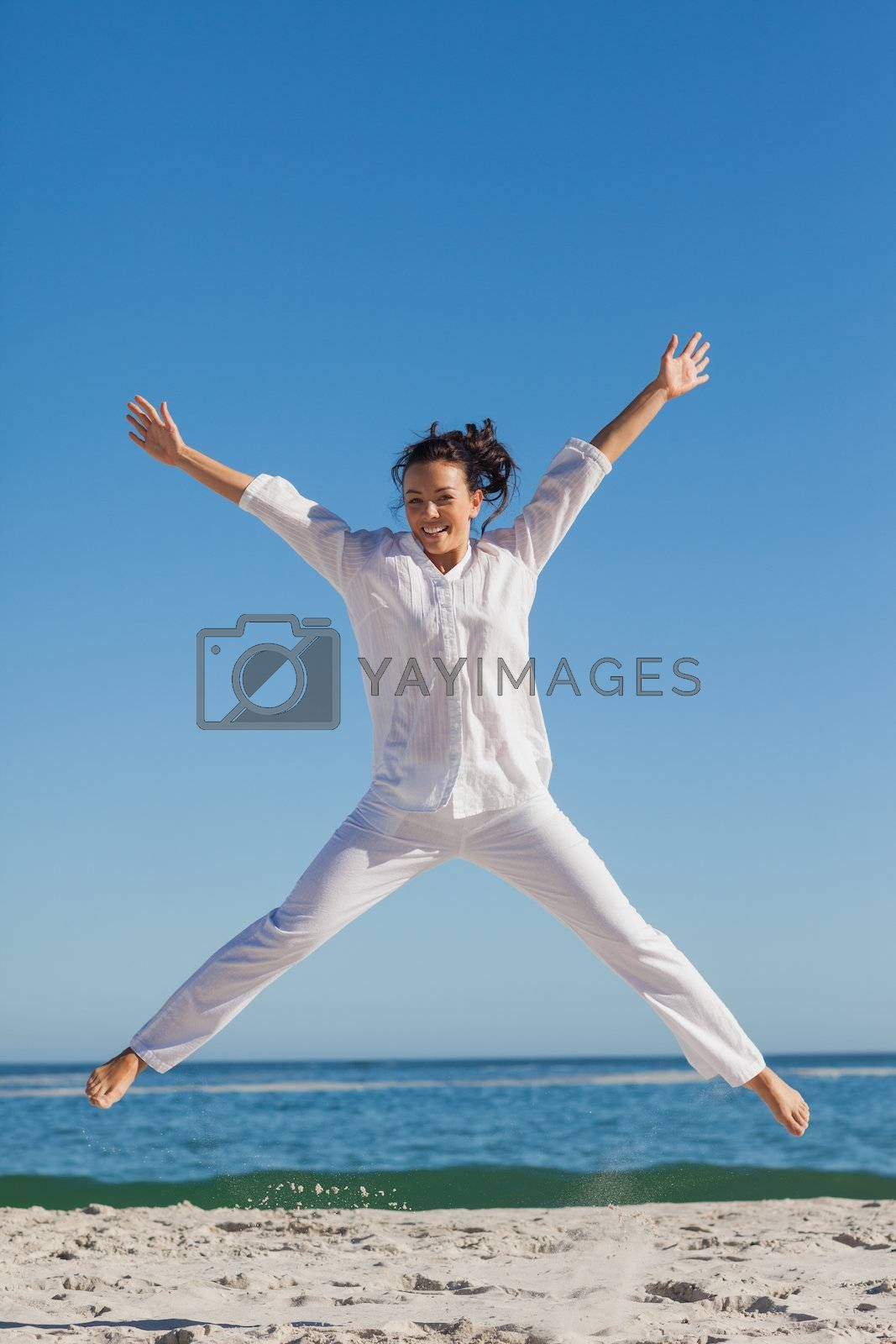 Smiling woman jumping up by Wavebreakmedia
