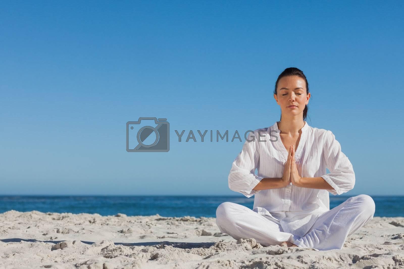 Peaceful woman practicing yoga on the beach by Wavebreakmedia