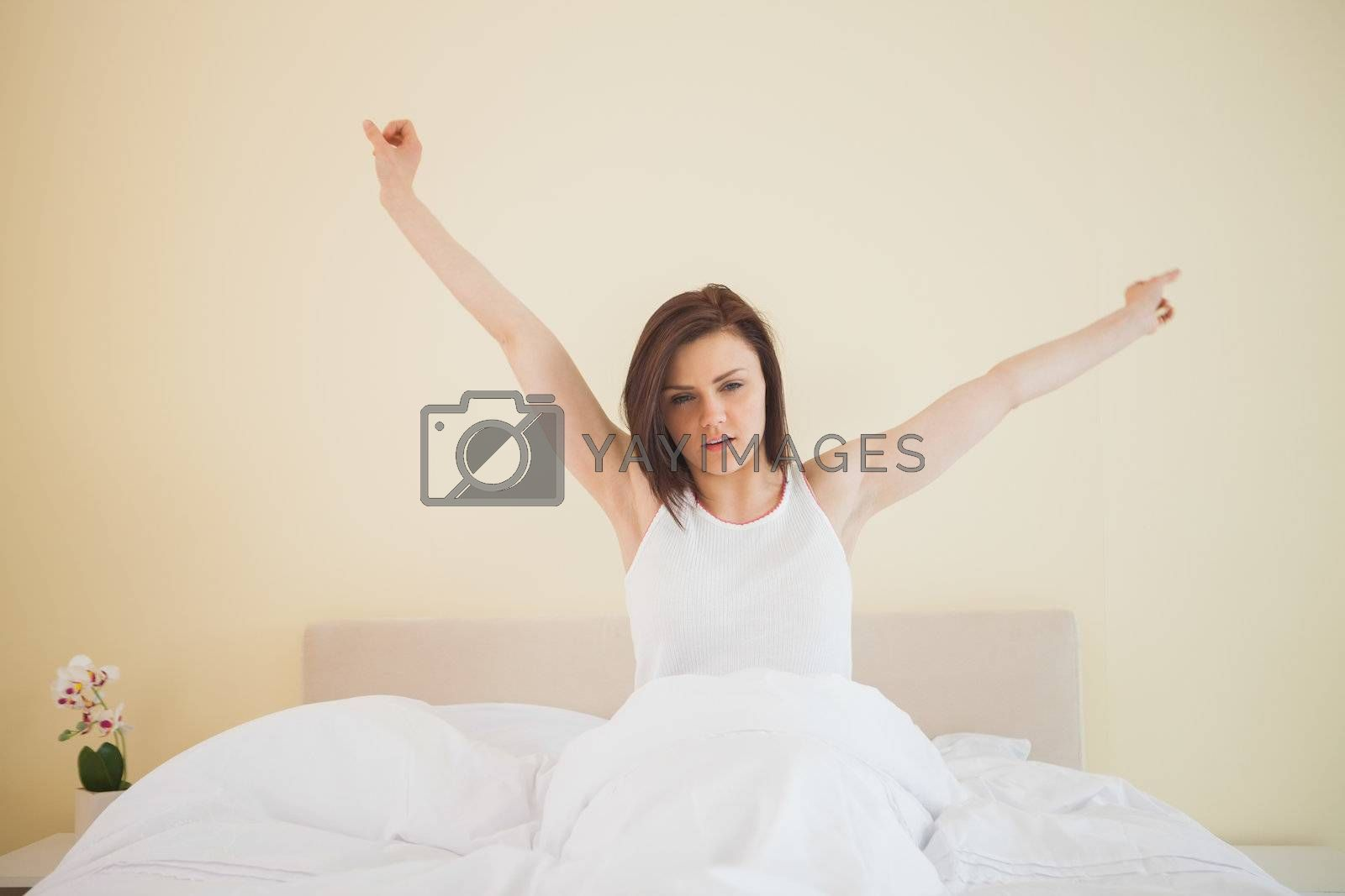 Awakened girl stretching in her bed by Wavebreakmedia