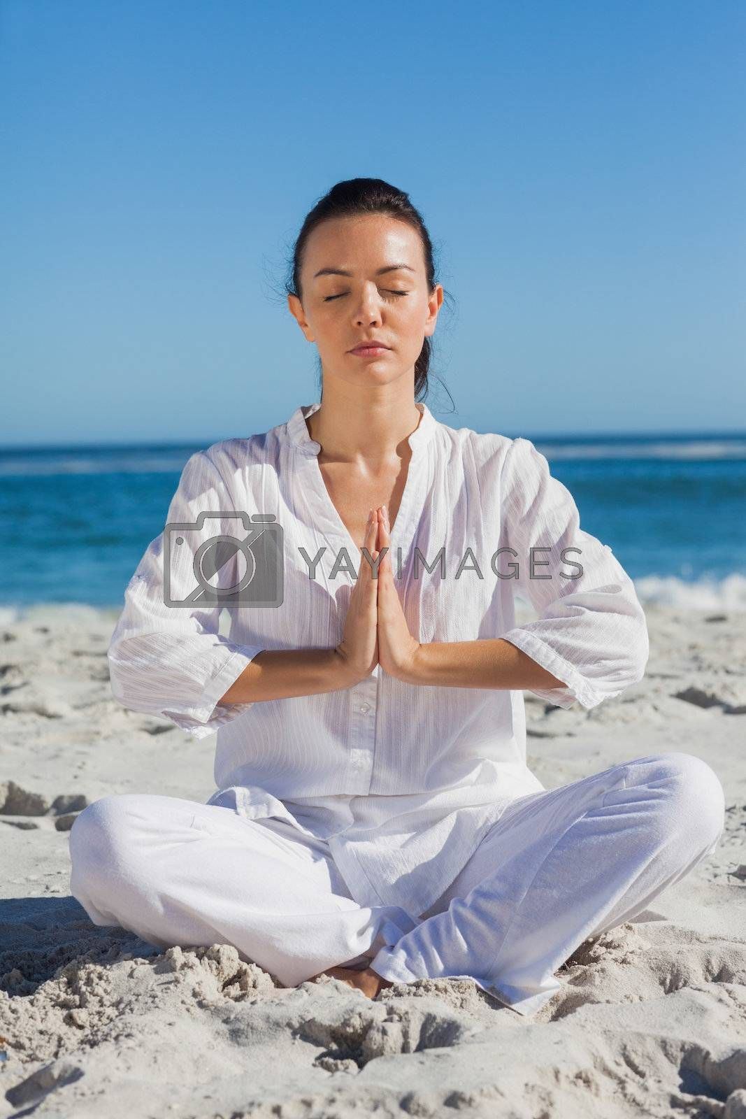 Woman practicing yoga at the beach by Wavebreakmedia