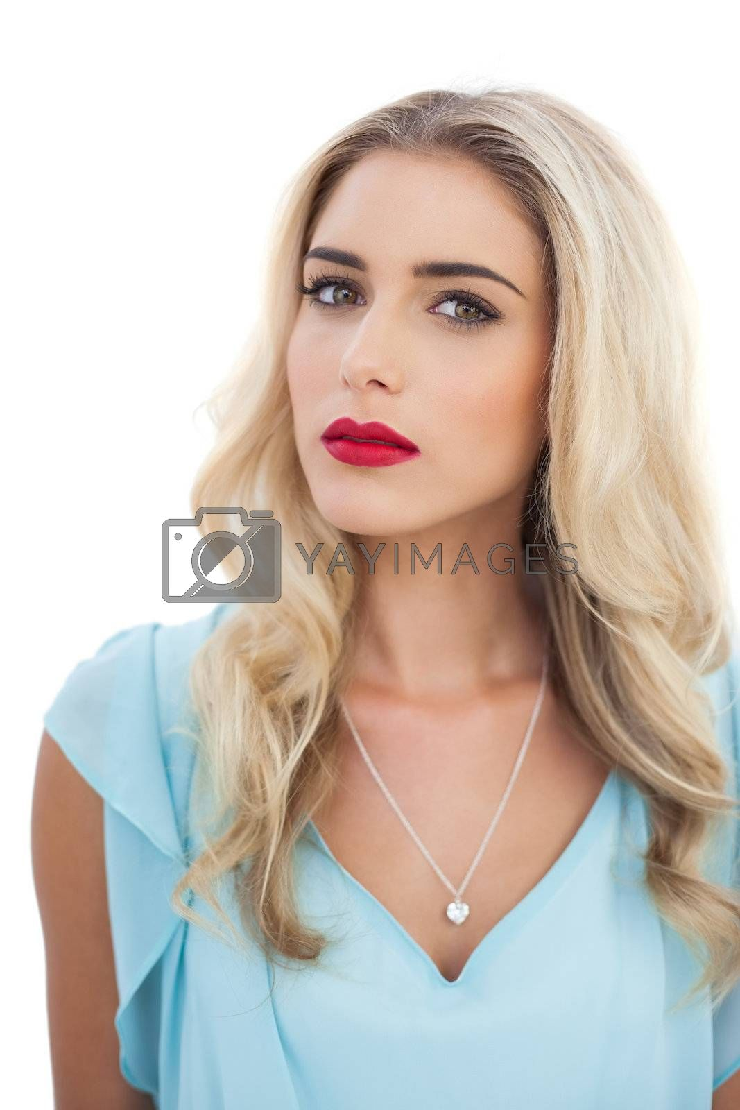 Thoughtful blonde model in blue dress looking at camera by Wavebreakmedia