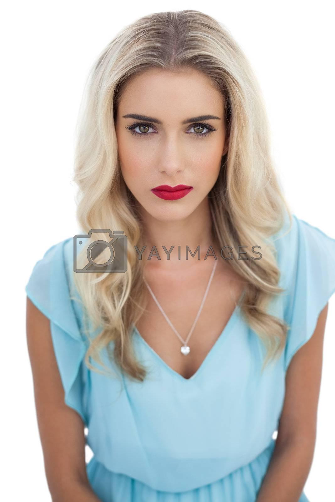 Severe blonde model in blue dress looking at camera by Wavebreakmedia