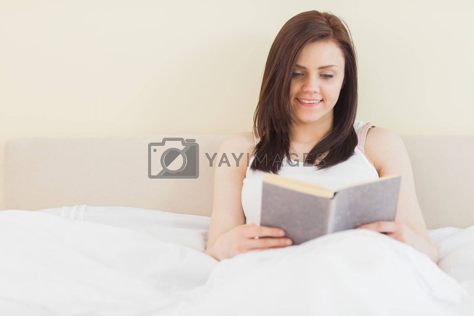 Smiling girl reading a book lying on bed by Wavebreakmedia