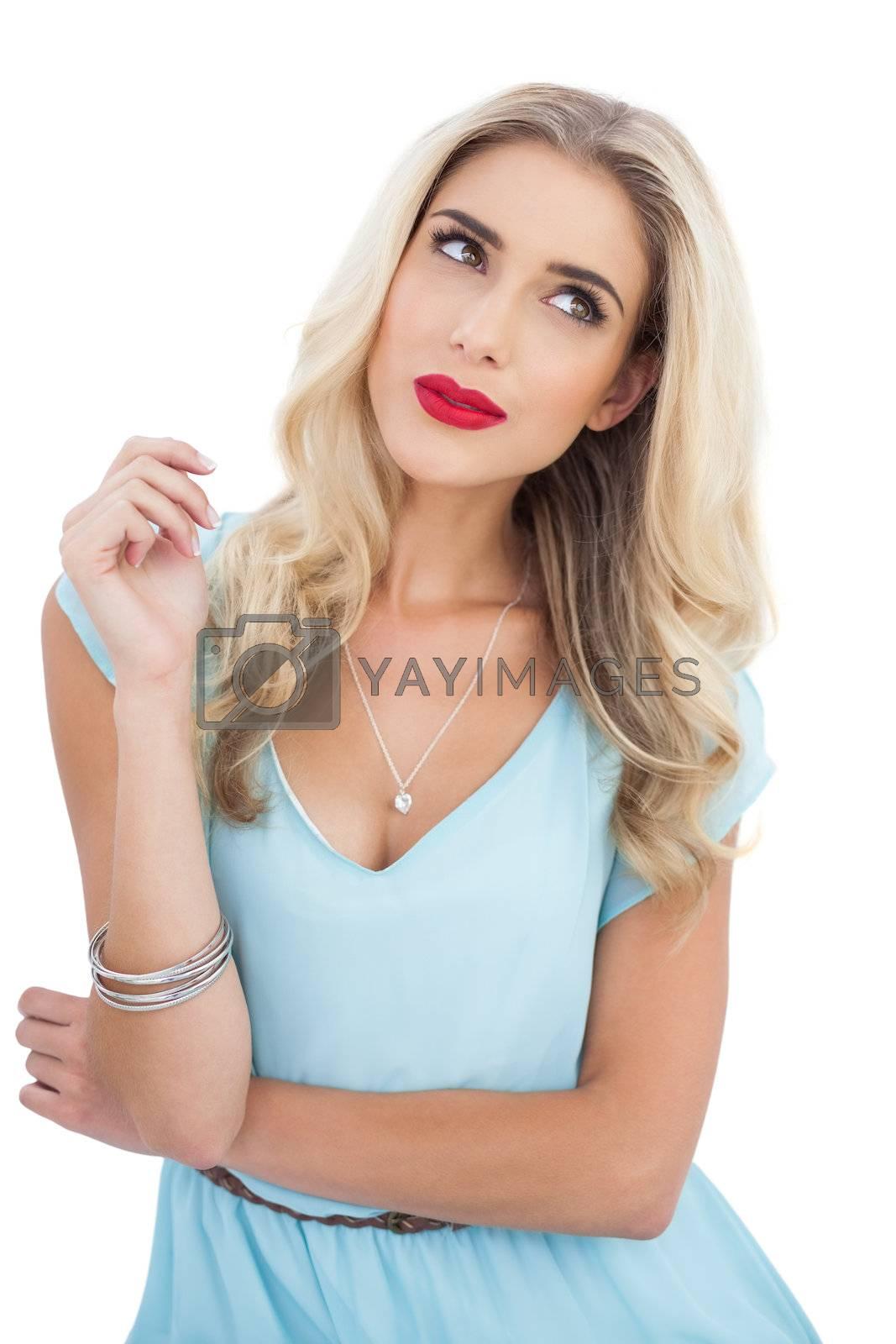 Seductive blonde model in blue dress looking away by Wavebreakmedia