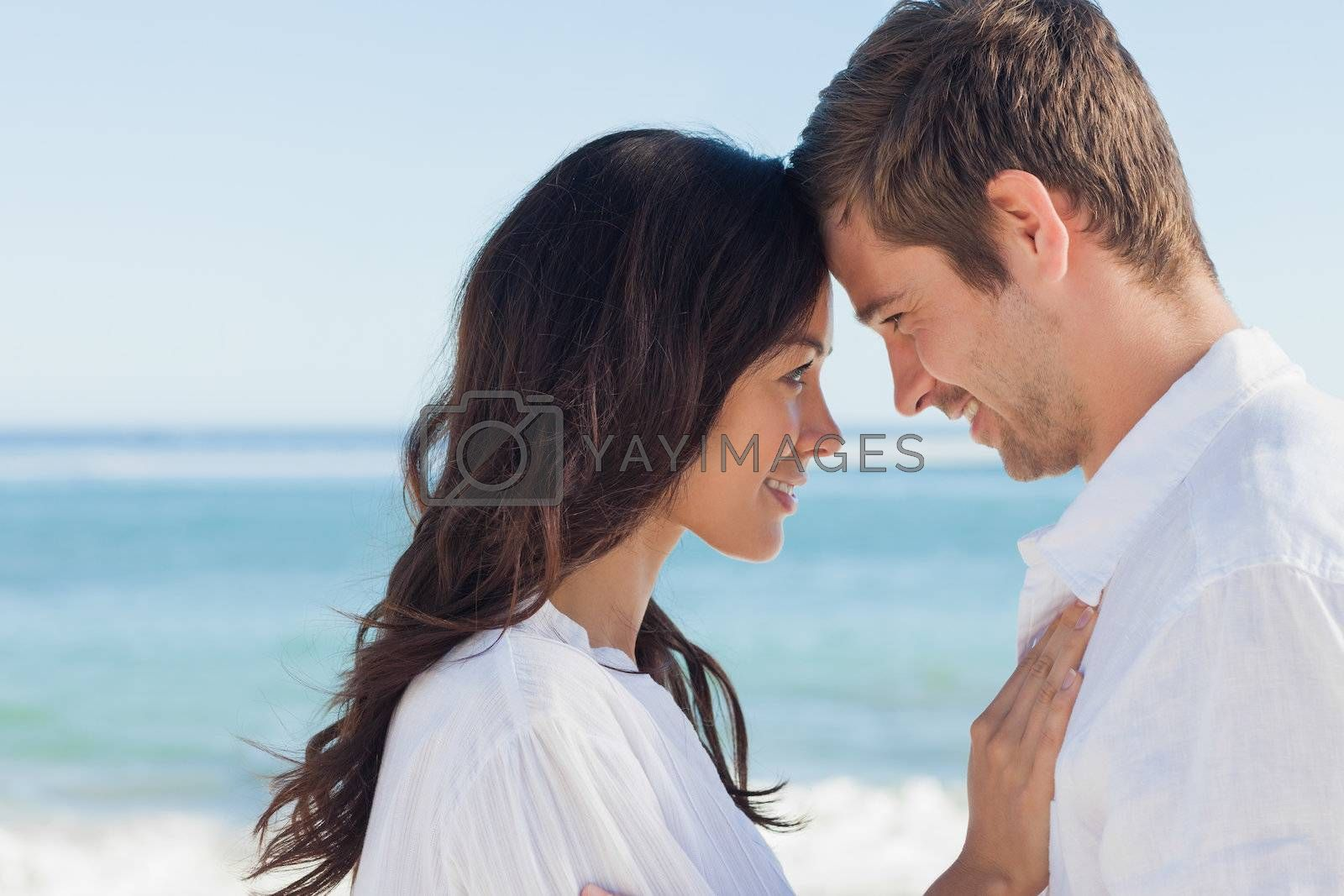 Attractive couple embracing on the beach  by Wavebreakmedia