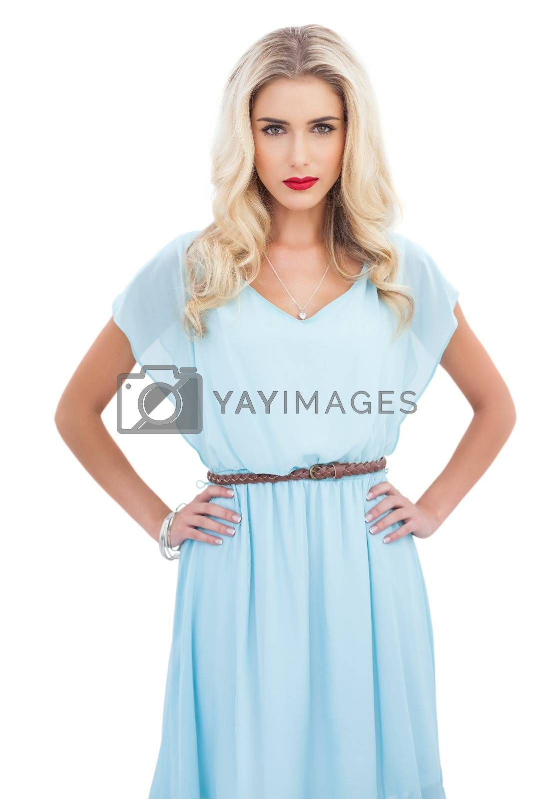 Contemplative blonde model in blue dress posing with hands the on hips by Wavebreakmedia