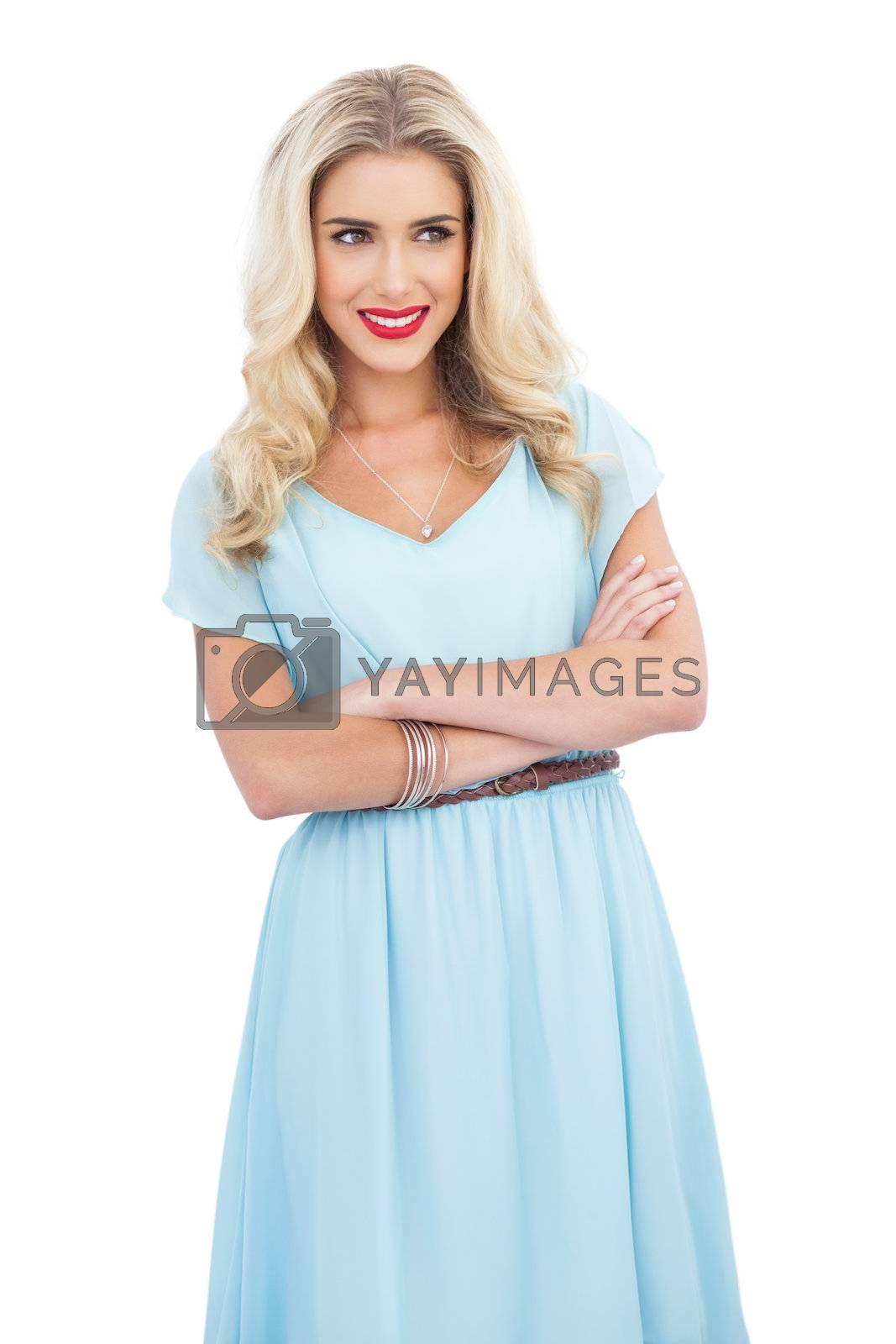 Smiling blonde model in blue dress posing crossed arms by Wavebreakmedia