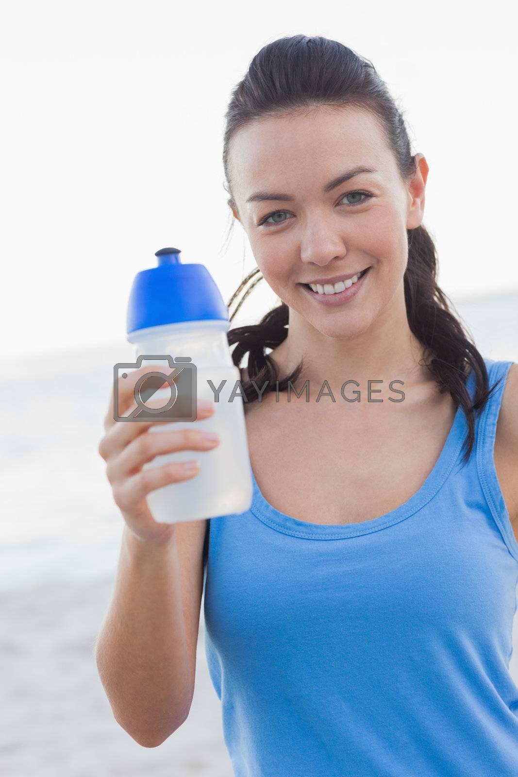 Smiling woman showing her water bottle by Wavebreakmedia