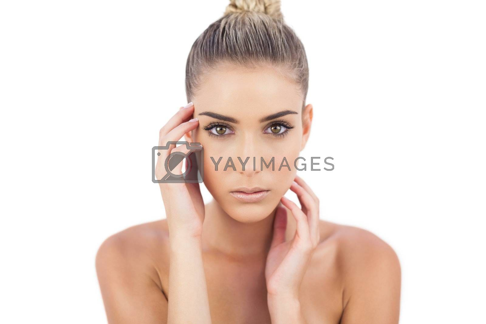 Cute woman holding her head and looking at camera by Wavebreakmedia