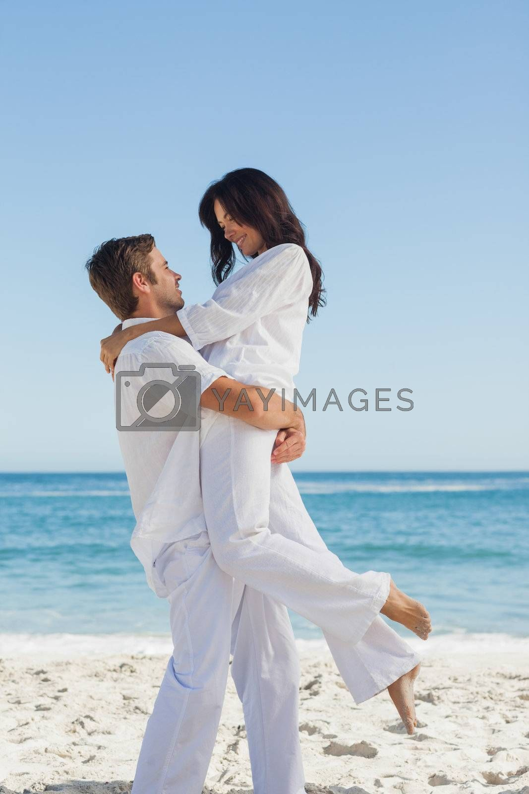 Happy man holding woman in arms by Wavebreakmedia