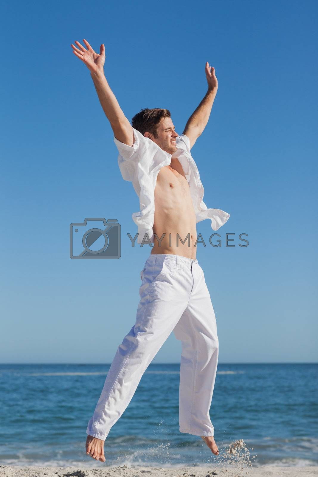 Attractive man jumping on beach by Wavebreakmedia