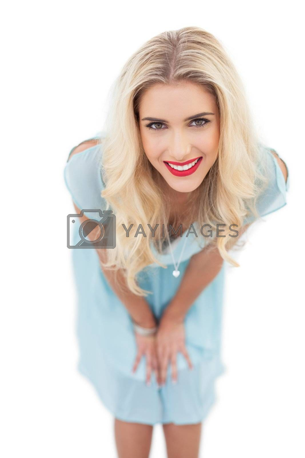 Happy blonde model in blue dress posing hands on the thighs by Wavebreakmedia