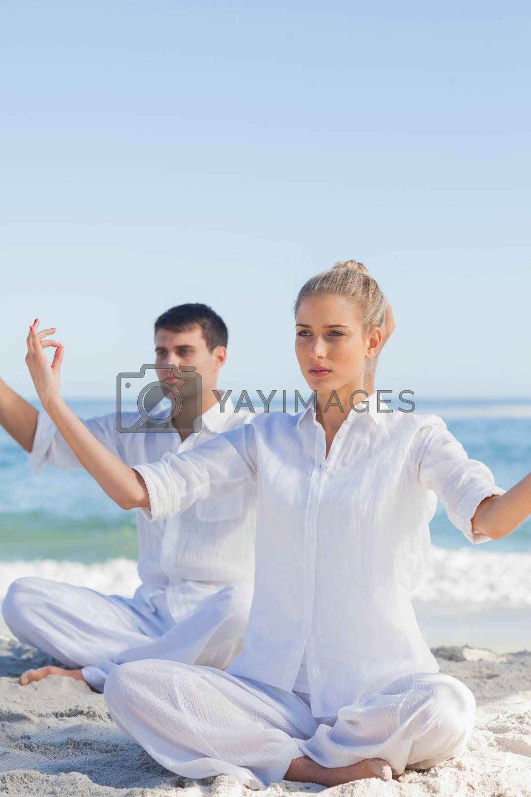 Attractive people doing yoga exercises by Wavebreakmedia