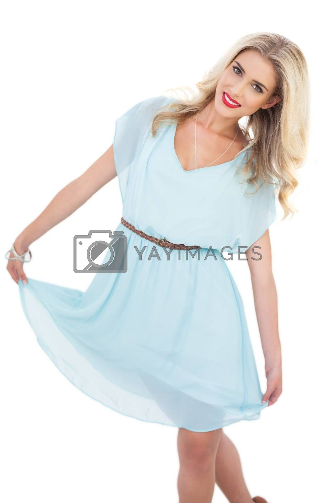 Delighted blonde model in blue dress posing holding her dress by Wavebreakmedia