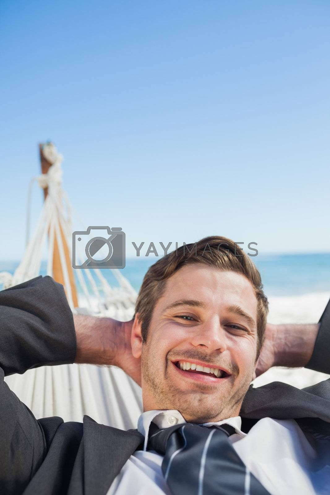 Smiling businessman relaxing in hammock by Wavebreakmedia