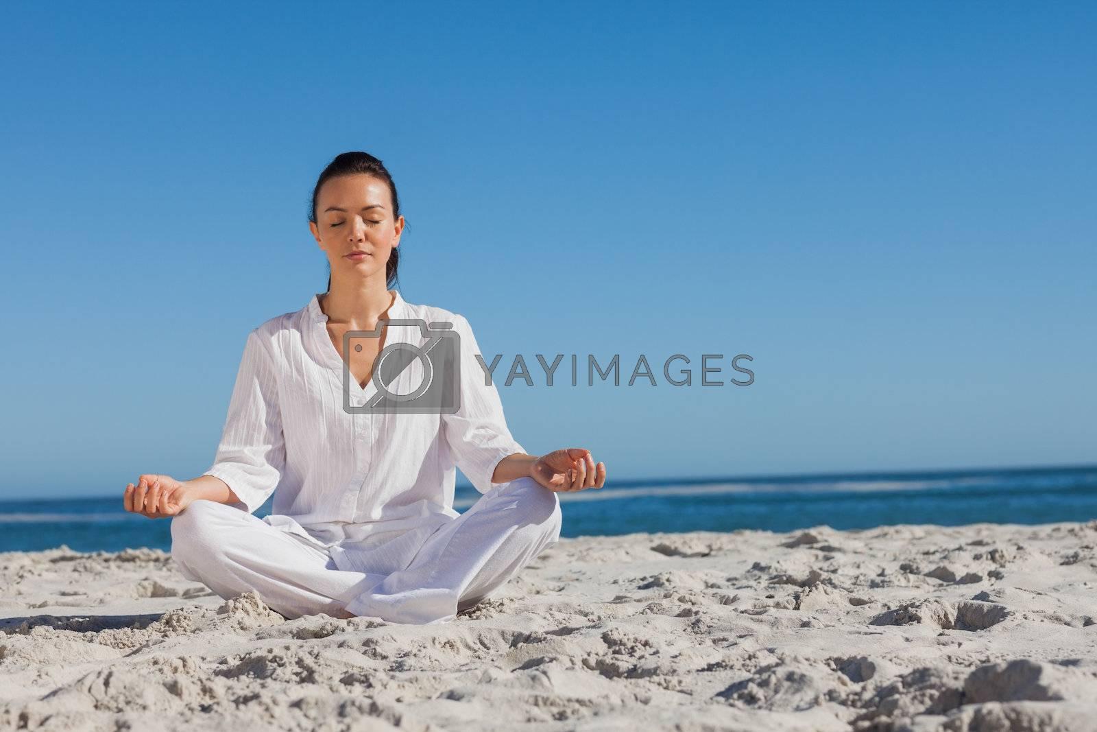 Woman in white doing yoga on the beach by Wavebreakmedia