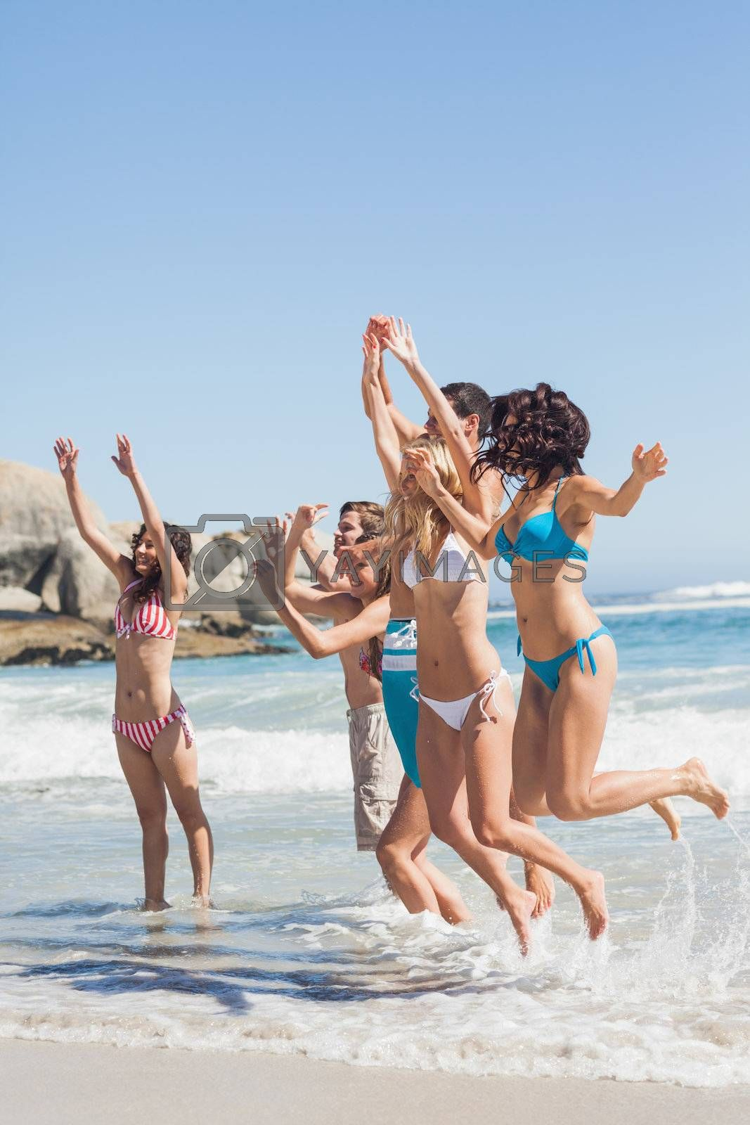 Side view of leaping friends at the beach by Wavebreakmedia
