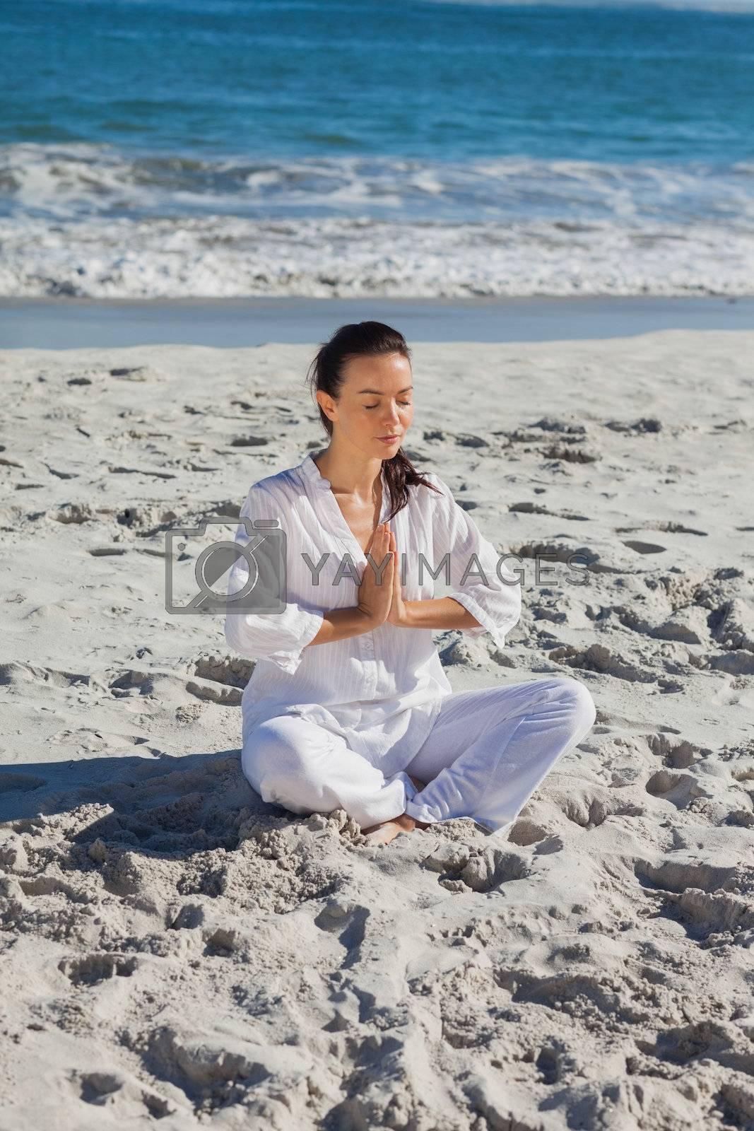 Peaceful woman practicing yoga against the sea by Wavebreakmedia